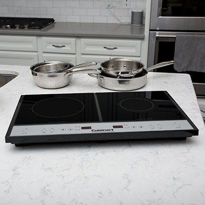 CUISINART <sup>&reg;</sup> Double Induction Cooktop - Two burner induction cooktop heats up faster and uses 70% less energy than conventional cooktops. Left burner has 8 heat settings and right burner offers 5 heat settings.  Sleek glass top design and bright LED timer display. Heat automatically stops 30 seconds after pot or pan is removed from burner.