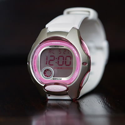 CASIO<sup>®</sup> Women's Digital Watch - This digital women's watch has a white band with silver case and pretty pink dial. Features include an alarm, stopwatch, dual time, LED light and date display. Water resistant to 50 meters.